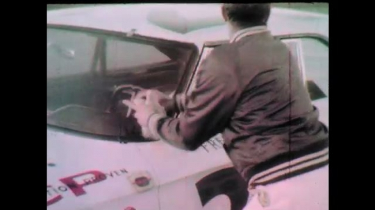 1960s: Man wipes windshield of race car.  Car pulls away.  Race cars speed down track.  Pit crew waits.