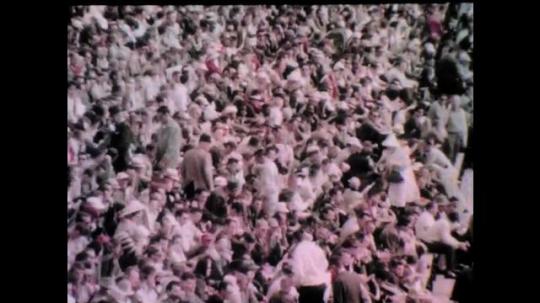 1960s: Spectators in stands.  Race car enters winner