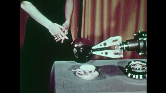 1950s: Woman stands next to mechanical hand that pours cup of coffee. Hands with string. Gloved hands at operating table, one points, one gives instrument.