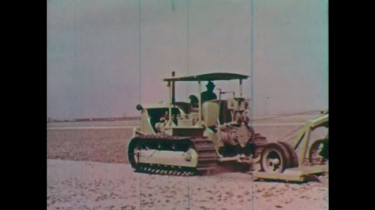 1950s: Tractor plows land. Dam.