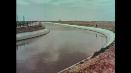 1950s: Man looks at canal. River flows through valley.