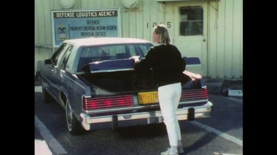 1970s: Woman shuts and locks trunk of car, looks around. Woman walks into office, walks out with man in uniform and points to car. Woman hands man keys to car.