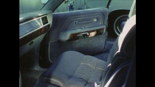 1970s: Uniformed man opens passenger side of car, opens glove box and searches inside. Man closes glove box, searches under seat and in seat cushions. Man closes car door.