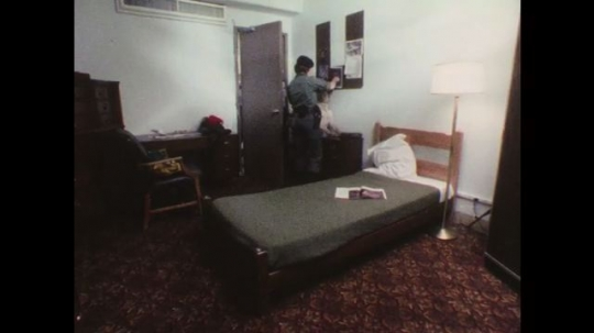 1970s: Uniformed woman guides dog through room, dog sniffs. Dog sniffs mattress, man swallows nervously. Man shakes head, dog noses under mattress. Woman pets dog.