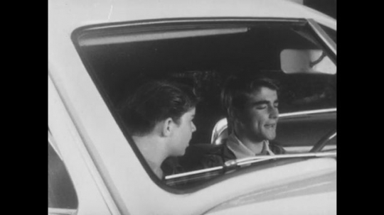 1950s: UNITED STATES: boys talk in car. Boy drives away from car. Man sees boys hot car. Car drives off
