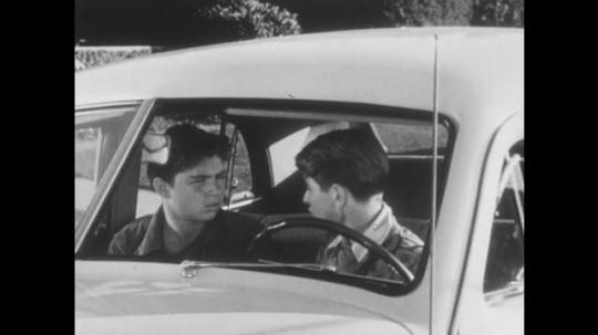 1950s: UNITED STATES: boys talk in car. Boys argue. Boy sits behind steering wheel. View through windscreen of boys.