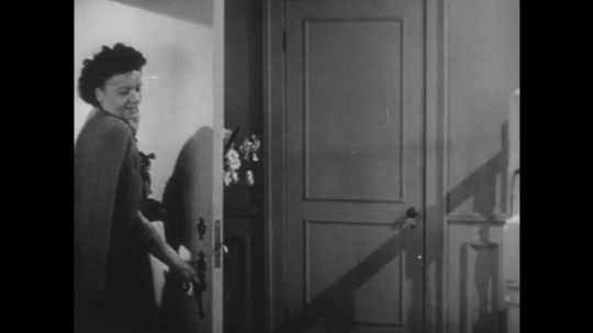 1950s: UNITED STATES: family arrive home. Girl goes upstairs. Man speaks to boy. Boy speaks to parents in hallway. Man smokes pipe