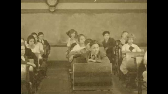 1920s: Students in class nod their heads. Teacher talks to class. Title card appears. Hand writes on paper with pen. Teacher approaches girl at her desk and hands her piece of paper.