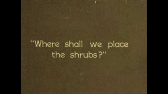 1920s: Title card. Teacher and students surround table with diorama of building on it. Teacher places signs for shrubs in diorama. Teacher places sign for garden in diorama, and athletic field.