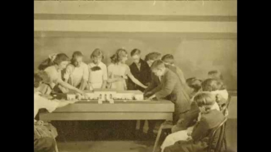 1920s: Students gathered around table with diorama of building on it. Teacher approaches. Entrance of diorama building. Sign for shrubs. Landscape around building. Teacher talks to students.