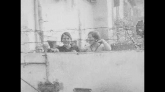 1940s: Women looking over fence. Man and woman in yard. Women behind fence, people in yard. Man woman and boy in front of house.