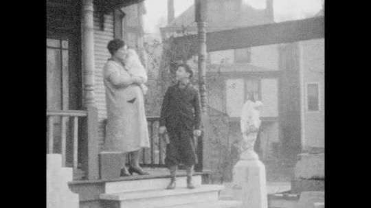 1940s: Woman with baby on porch with boy, boy walks away, walks down street. Woman walks to camera, close up of woman with baby. Woman rocking baby.