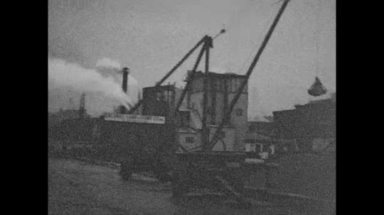 1940s: View of factory, crane lifting materials. Pan across factory.