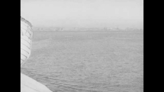 1940s: View from ship, pan of coastline. People on ship deck. View of houses from car. View of coastline.