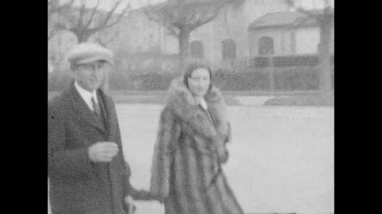 1940s: Man and woman walk down street with boy. Woman shakes man
