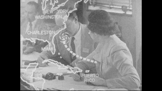 1950s: Animation of hurricane spinning off the East Coast superimposed over people talking and thinking at conference table. Command center meeting at Emergency Warning Center.
