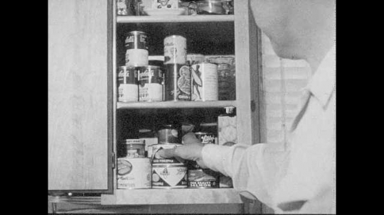 1950s: Man inspects canned goods in cupboard. Boy brings lantern and camping stove to man in kitchen.