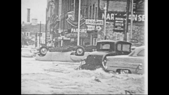 1950s: Flooded streets of city. Destroyed and sunken boats. Large tree fallen on house, crushing the roof.