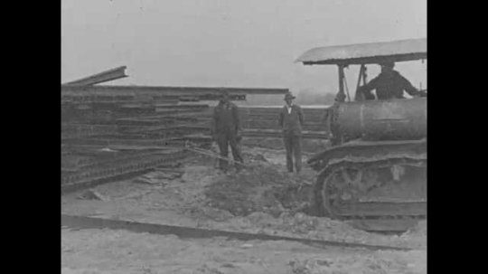 1920s: A tractor pulls a metal rail out of a stack, then it hauls a pile of lumber bound by a rope.