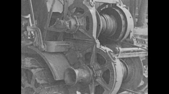 1920s: A cable wind around a reel on a piece of machinery. A drag-line bucket attached to the cable dredges through a river. A man operates the control levers. The bucket pulls earth to the surface.