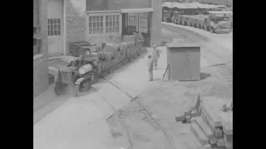 1920s: An industrial railroad hauls materials out of a building led by a tractor. Intertitle: