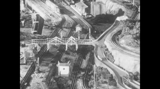 1950s: Multiple model trains pass through busy interchanges and under bridges. Model railroad executives examine model train cars in a boardroom.