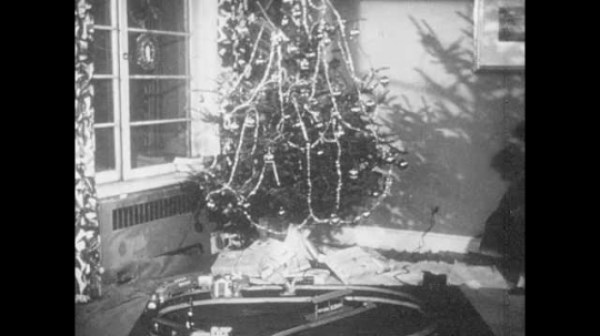 1950s: Boy and girl turn on model train under Christmas tree. Mother and Father smile and join children at the model train set. Father tries to run controller and boy stops him.