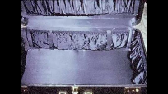1950s:  empty suitcase. Lady closes suitcase. Man lifts suitcase. Man weighs suitcase. Passengers arrive at plane
