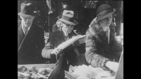 New York City 1940s: Customers examine goods at a lower east side market. Chinatown. Street signs read