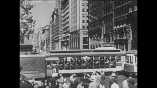 New York City 1940s: Crowds and traffic at Fifth Avenue and West 42nd Street. The New York Public Library Main Branch. A man sits out front, feeding pigeons.