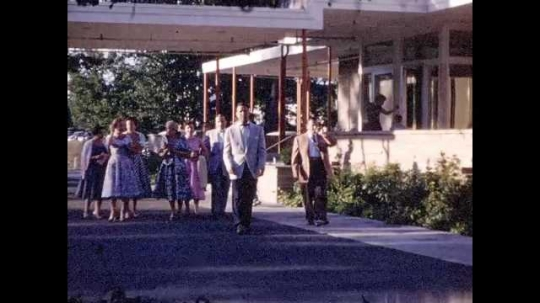 1950s: Group of well-dressed couples outside of building. Building exterior, smiling couple couples exit and wave.
