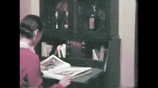1950s: Woman at bureau/cabinet reading magazine. Trophies in display cabinet. Twin beds in (hotel?) room.