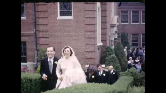1950s: Wedding party and guests ascend staircase, ornate church behind them. Woman poses and smiles. Woman smiles and waves. People walk by, some linger near car.