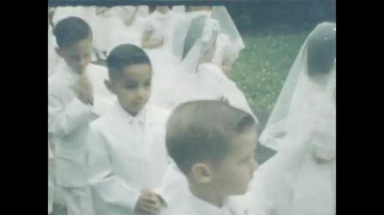 1950s: Line of boys and line of girls, dressed in white, walk with hands in praying pose, nun weaves through line. Line of girls in white, adult woman trials end. Line of boys and girls, boy smiles.