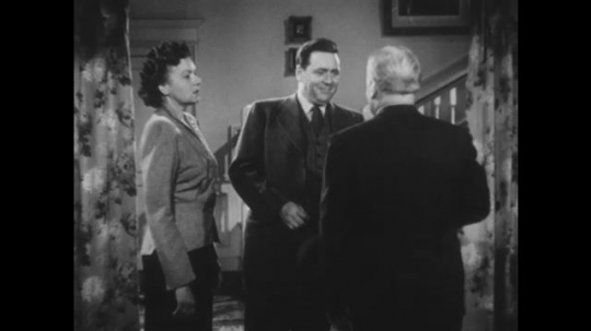 1950s: UNITED STATES: men speak in lounge. Man shows paper to lady and man in house. Lady looks shocked
