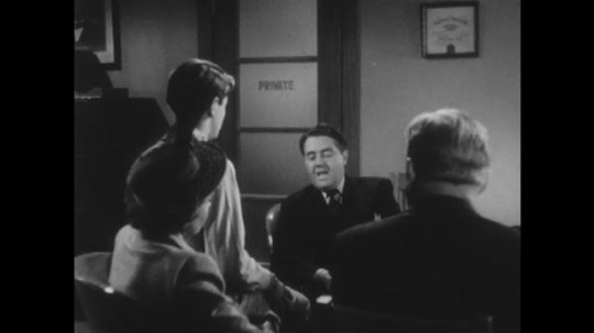 1950s: UNITED STATES: man speaks to boy in office. Boy leaves room. Man speaks to parents of boy.