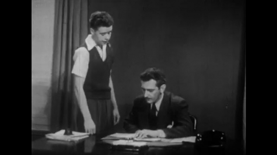 1940s: Teenage boy and man look at paper.  Boy points and speaks.  Man sits at desk.