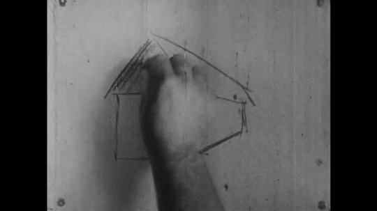 1960s: Man adds shading onto simple drawing of a house. Person draws lines using triangular ruler.