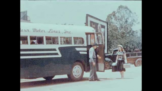 1940s: UNITED STATES: lady gives bags to bus driver. Ladies leave town. Women wave at bus.