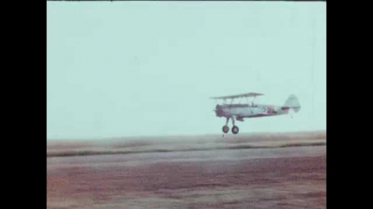 1940s: UNITED STATES: plane flies over cotton fields. Machine in cotton field. Two men walk and talk in town. Industrial buildings in town