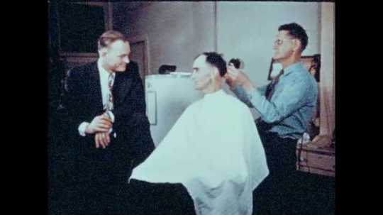 1940s: UNITED STATES: man gets hair cut in barbers shop. Close up of cheques. Graph shows total amount of funds raised.