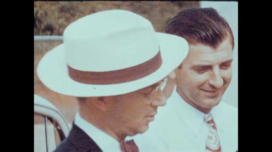 1940s: UNITED STATES: man in hat. Man speaks on radio. Man speaks on telephone, People shake hands. Ladies talk.