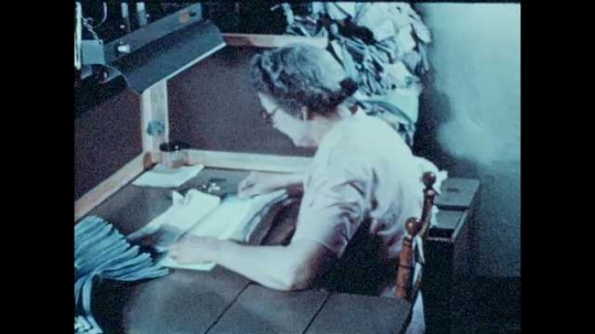 1940s: UNITED STATES: lady inspects sewing at table. Lady looks at stitches and details on fabric.