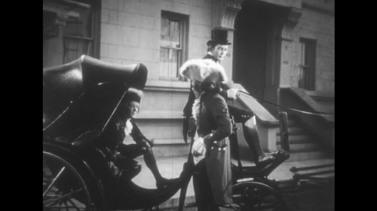 1950s: Man sits in horse-drawn carriage, talks to another man who stands, horse-drawn carriage starts to move. Three men stand around man who sits, talks and writes, they wear Victorian clothing.