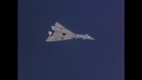1960s: Supersonic plane flies through sky. Text on screen. Fighter jet lifts off of landing pad. Jet flies through sky.