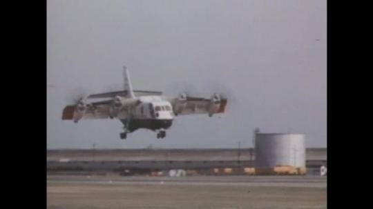 1960s: Large propeller plane lifts from runway. Plane hovers in air. Men lift model of plane. Model of plane flies in sky. Man with binocular headset. Model plane twists in sky.