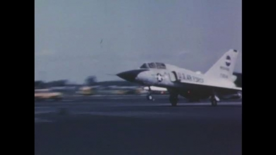1960s: Fighter jet rolls down runway. Fighter jet flies in sky. Construction vehicle cuts grooves into runway. Hand points to grooves in concrete. Commercial airliner lands on wet runway.