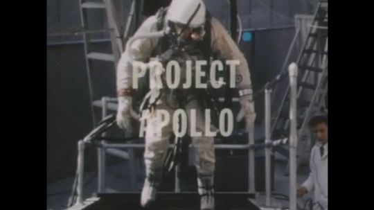 1960s: Text on screen. Man in space suit runs on treadmill. Astronaut trains in sideways chair. Spacecraft hovers. Man trains in cockpit. Men train with parachutes. Nosecone is lifted onto ship.
