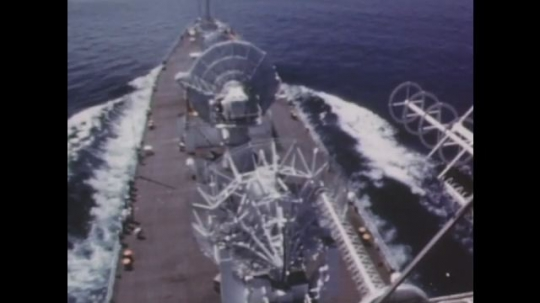 1960s: Naval ship cuts through water. Antenna array turns upward. Satellite dish. Space capsule floats in ocean. Men exit helicopter to deck of ship. Text on screen Rocket ignites on launch pad.