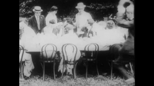 1910s: Two men jostle to sit next to a woman at a picnic table, knocking over a boy. They compete to fill her plate with food. Her plate is full. The rest of the people at the table laugh.